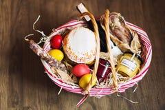 Ζωηρόχρωμα αυγά Πάσχας σε ένα καλάθι με το κέικ, το κόκκινο κρασί, hamon ή το jerky και ξηρό καπνισμένο λουκάνικο στο ξύλινο υπόβ Στοκ φωτογραφίες με δικαίωμα ελεύθερης χρήσης