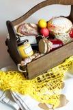 Ζωηρόχρωμα αυγά Πάσχας σε ένα καλάθι με το κέικ, το κόκκινο κρασί, hamon ή το jerky και ξηρό καπνισμένο λουκάνικο στο άσπρο υπόβα Στοκ φωτογραφίες με δικαίωμα ελεύθερης χρήσης