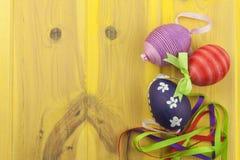 Ζωηρόχρωμα αυγά Πάσχας σε ένα παλαιό κίτρινο ξύλινο υπόβαθρο Διακοπές εορτασμού Πάσχα σύμβολο Πάσχας Στοκ φωτογραφία με δικαίωμα ελεύθερης χρήσης