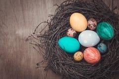 Ζωηρόχρωμα αυγά Πάσχας σε μια φωλιά σε ένα αγροτικό ύφος Στοκ Φωτογραφίες