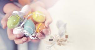 Ζωηρόχρωμα αυγά Πάσχας στα χέρια παιδιών Στοκ Εικόνες