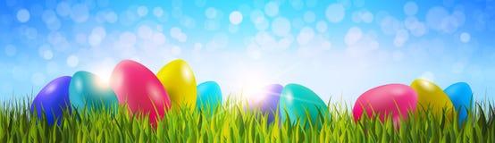 Ζωηρόχρωμα αυγά Πάσχας στην πράσινη χλόη πέρα από το μπλε οριζόντιο έμβλημα υποβάθρου Bokeh ελεύθερη απεικόνιση δικαιώματος
