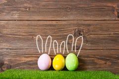 Ζωηρόχρωμα αυγά Πάσχας στη χλόη με τα χρωματισμένα αυτιά κουνελιών στο ξύλινο υπόβαθρο Στοκ Φωτογραφίες
