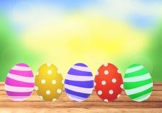 Ζωηρόχρωμα αυγά Πάσχας στον ξύλινο πίνακα πέρα από τη φύση Στοκ Φωτογραφίες