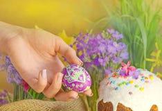 Ζωηρόχρωμα αυγά Πάσχας στο θηλυκό χέρι Χέρια που κρατούν το αυγό Πάσχας Στοκ Φωτογραφίες