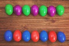 Ζωηρόχρωμα αυγά Πάσχας στο καφετί ξύλινο υπόβαθρο Στοκ φωτογραφίες με δικαίωμα ελεύθερης χρήσης