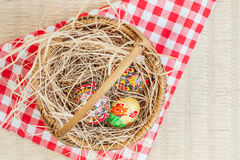 Ζωηρόχρωμα αυγά Πάσχας στο καλάθι Στοκ Εικόνα