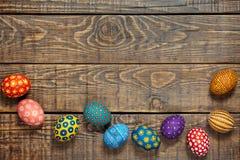 Ζωηρόχρωμα αυγά Πάσχας στο ξύλινο υπόβαθρο με το διάστημα Στοκ Εικόνα