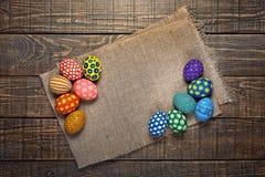 Ζωηρόχρωμα αυγά Πάσχας sackcloth στο κέντρο - ξύλινο υπόβαθρο Στοκ εικόνα με δικαίωμα ελεύθερης χρήσης