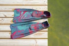 Ζωηρόχρωμα βατραχοπέδιλα για την κατάδυση στην ξύλινη αποβάθρα στοκ φωτογραφία