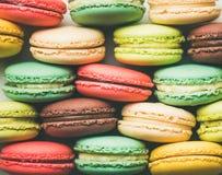 Ζωηρόχρωμα γαλλικά macaroons μπισκότα που συσσωρεύονται στις σειρές στοκ φωτογραφία