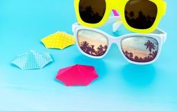 Ζωηρόχρωμα γυαλιά ηλίου και parasol στο ανοικτό μπλε υπόβαθρο στούντιο Στοκ φωτογραφία με δικαίωμα ελεύθερης χρήσης