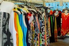 Ζωηρόχρωμα γυναικεία ενδύματα στις κρεμάστρες ενδυμάτων σε μια αγορά Στοκ Εικόνες