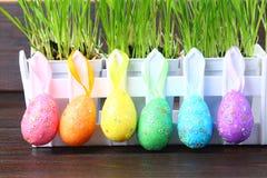 Ζωηρόχρωμα διακοσμητικά αυγά των χρωμάτων ουράνιων τόξων σε ένα υπόβαθρο της πράσινης χλόης Πάσχα Στοκ Εικόνες