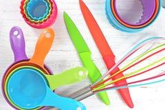 Ζωηρόχρωμα εργαλεία κουζινών στο άσπρο αγροτικό υπόβαθρο Στοκ Εικόνα