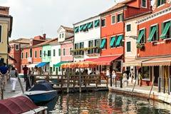 Ζωηρόχρωμα ζωηρόχρωμα σπίτια και καταστήματα παράλληλα με το κανάλι στο νησί Burano, στην ενετική λιμνοθάλασσα, Ιταλία Στοκ Εικόνες