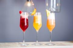 Ζωηρόχρωμα θερινά κοκτέιλ με Prosecco, είδος τρία από τα κοκτέιλ φρούτων - σμέουρο, ροδάκινο και ανανάς, οριζόντια ταπετσαρία Στοκ Φωτογραφία