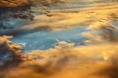 Ζωηρόχρωμα θεϊκά πορτοκαλιά σύννεφα στον ουρανό στο ηλιοβασίλεμα Στοκ Εικόνες