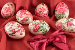 Ζωηρόχρωμα διακοσμημένα decoupage αυγά Πάσχας στο κόκκινο ύφασμα Στοκ Φωτογραφία