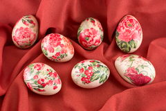 Ζωηρόχρωμα διακοσμημένα decoupage αυγά Πάσχας στο κόκκινο ύφασμα Στοκ Εικόνα