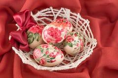 Ζωηρόχρωμα διακοσμημένα decoupage αυγά Πάσχας στο κόκκινο ύφασμα Στοκ φωτογραφίες με δικαίωμα ελεύθερης χρήσης