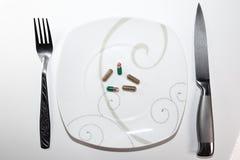 Ζωηρόχρωμα κάψες και χάπια στο πιάτο με το δίκρανο και μαχαίρι στο άσπρο υπόβαθρο Στοκ Εικόνες