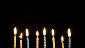 Ζωηρόχρωμα καίγοντας κεριά μήκους σε πόδηα που τίθενται στο μαύρο υπόβαθρο 4K φιλμ μικρού μήκους