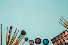 Ζωηρόχρωμα καλλυντικά στον μπλε εργασιακό χώρο με το διάστημα αντιγράφων Τα καλλυντικά αποτελούν τα αντικείμενα καλλιτεχνών: σκιέ Στοκ εικόνες με δικαίωμα ελεύθερης χρήσης