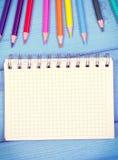 Ζωηρόχρωμα κραγιόνια και σημειωματάριο στους πίνακες, σχολικά εξαρτήματα, διάστημα αντιγράφων για το κείμενο Στοκ εικόνα με δικαίωμα ελεύθερης χρήσης