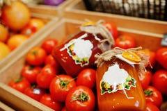 Ζωηρόχρωμα λαμπρά φρέσκα λαχανικά Ντομάτες με την κονσερβοποίηση hommemade και χειροποίητος χυμός ντοματών στο ράφι μιας υπεραγορ στοκ φωτογραφία