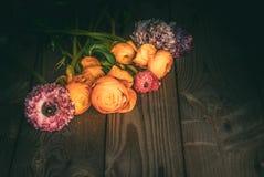 Ζωηρόχρωμα λουλούδια που διασκορπίζονται σε ένα αγροτικό ξύλινο υπόβαθρο στοκ φωτογραφία