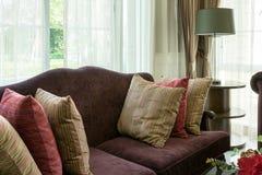 Ζωηρόχρωμα μαξιλάρια στον κόκκινο καναπέ στο καθιστικό πολυτέλειας Στοκ Εικόνες