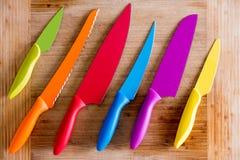Ζωηρόχρωμα μαχαίρια κουζινών στον ξύλινο τέμνοντα πίνακα Στοκ εικόνα με δικαίωμα ελεύθερης χρήσης