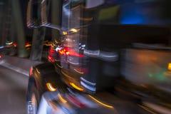 Ζωηρόχρωμα μεγάλα φω'τα φορτηγών εγκαταστάσεων γεώτρησης ημι που συναγωνίζονται τη νύχτα πέρα από τη γέφυρα στοκ φωτογραφία με δικαίωμα ελεύθερης χρήσης