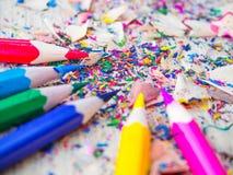 Ζωηρόχρωμα μολύβια με τα ζωηρόχρωμα ξέσματα μολυβιών στο ξύλινο υπόβαθρο Στοκ Φωτογραφίες
