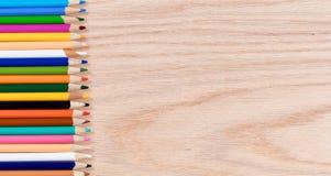 Ζωηρόχρωμα μολύβια που παρατάσσονται στο δρύινο ξύλινο υπολογιστή γραφείου Στοκ εικόνες με δικαίωμα ελεύθερης χρήσης