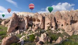 Ζωηρόχρωμα μπαλόνια ζεστού αέρα που πετούν πέρα από την κοιλάδα Zelve, Τουρκία Στοκ Εικόνες