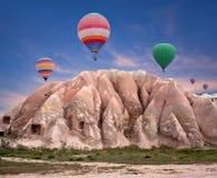 Ζωηρόχρωμα μπαλόνια ζεστού αέρα που πετούν πέρα από την κόκκινη κοιλάδα, Τουρκία Στοκ εικόνα με δικαίωμα ελεύθερης χρήσης