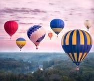 Ζωηρόχρωμα μπαλόνια ζεστού αέρα που πετούν πέρα από τον ποταμό και το δάσος Στοκ Φωτογραφία
