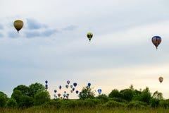 Ζωηρόχρωμα μπαλόνια ζεστού αέρα που πετούν πέρα από τον τομέα και τη λίμνη στο SUMM Στοκ εικόνες με δικαίωμα ελεύθερης χρήσης