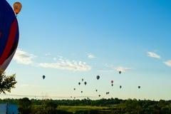 Ζωηρόχρωμα μπαλόνια ζεστού αέρα που πετούν πέρα από τον τομέα και τη λίμνη στο SUMM Στοκ φωτογραφία με δικαίωμα ελεύθερης χρήσης