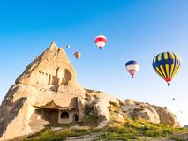 Ζωηρόχρωμα μπαλόνια ζεστού αέρα που πετούν πέρα από το τοπίο βράχου σε Cappadoc Στοκ Φωτογραφίες