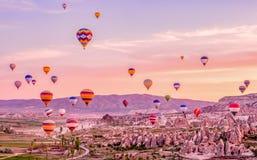 Ζωηρόχρωμα μπαλόνια ζεστού αέρα που πετούν πέρα από το τοπίο βράχου σε Cappadoc Στοκ Εικόνες