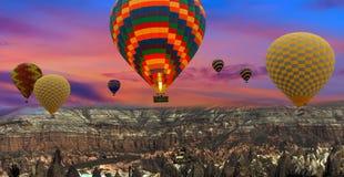 Ζωηρόχρωμα μπαλόνια ζεστού αέρα που πετούν πέρα από το τοπίο σε Cappadocia TU Στοκ εικόνα με δικαίωμα ελεύθερης χρήσης