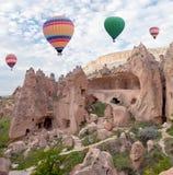 Ζωηρόχρωμα μπαλόνια ζεστού αέρα που πετούν πέρα από Cappadocia, Τουρκία Στοκ Εικόνες