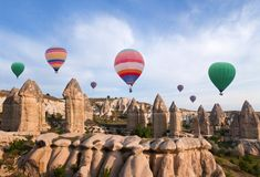 Ζωηρόχρωμα μπαλόνια ζεστού αέρα που πετούν πέρα από Cappadocia, Τουρκία Στοκ Φωτογραφία