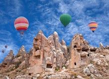 Ζωηρόχρωμα μπαλόνια ζεστού αέρα που πετούν πέρα από Cappadocia, Τουρκία Στοκ Φωτογραφίες