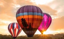 Ζωηρόχρωμα μπαλόνια ζεστού αέρα κοντά στον ορίζοντα ως σύνολα ήλιων στην έκθεση της Farmer ` s κομητειών του Warren στο 8/1/17 Στοκ εικόνα με δικαίωμα ελεύθερης χρήσης
