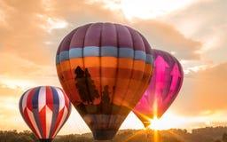 Ζωηρόχρωμα μπαλόνια ζεστού αέρα κοντά στον ορίζοντα ως σύνολα ήλιων στην έκθεση της Farmer ` s κομητειών του Warren στο 8/1/17 Στοκ Εικόνα
