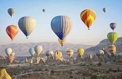 Ζωηρόχρωμα μπαλόνια ζεστού αέρα που πετούν πέρα από την κοιλάδα σε Cappadocia Στοκ φωτογραφίες με δικαίωμα ελεύθερης χρήσης